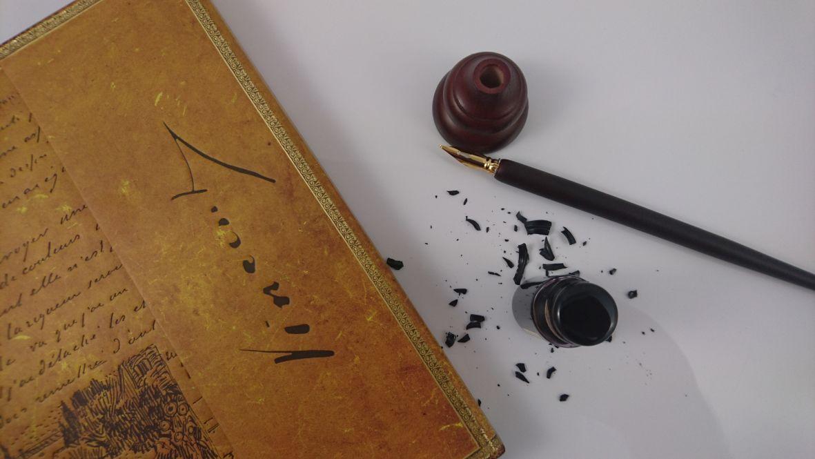 Feder mit Tinte und Schreibbuch