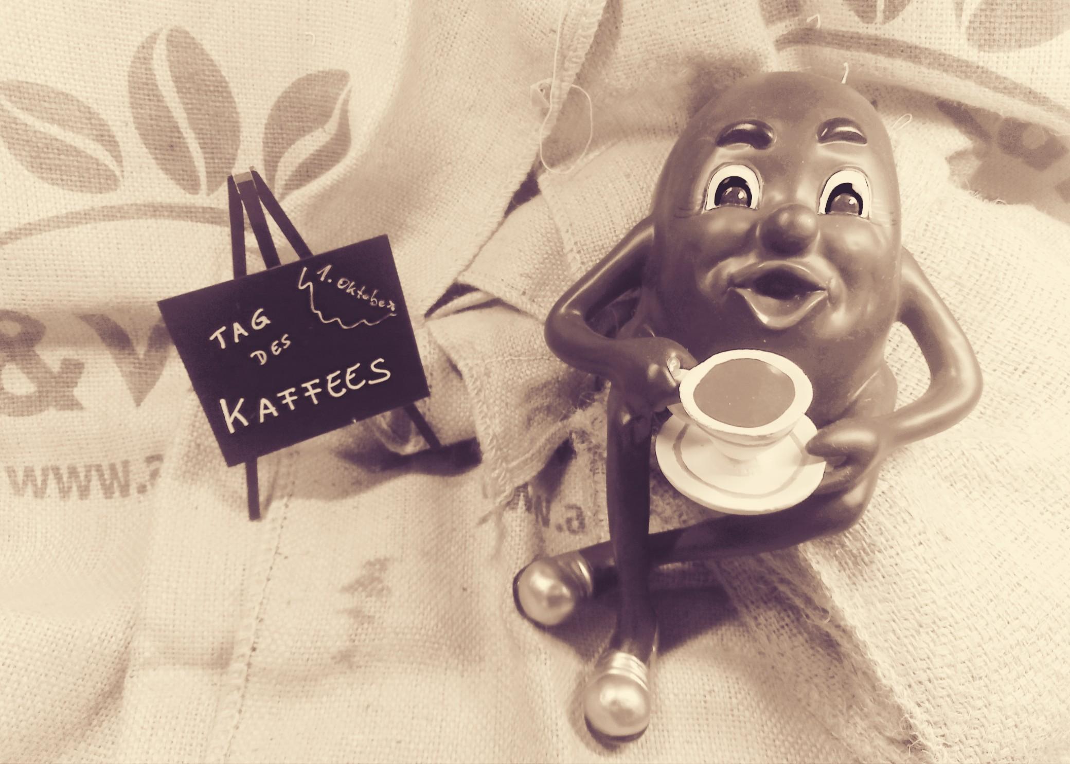 """zum """"Tag des Kaffees"""" sitzt eine Kaffeebohne mit einer Kaffeetasse auf einem Kaffeesack"""